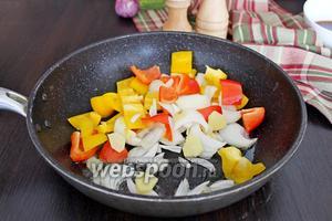 Добавить в сковороду лук и сладкий перец и, потряхивая сковороду, обжариваем на сильном огне 2 минуты.