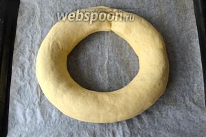 Рулет свернуть в кольцо, скрепить концы и переложить на противень, застеленный пекарской бумагой.
