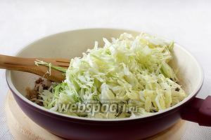 Добавить тонко нарезанную капусту. Посолить по вкусу, добавить перец. Помешивая, слегка поджарить мясо с капустой, а затем влить немного воды и потушить до мягкости.