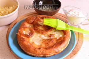 Затем смазать лепёшку с помощью кисти чесночным соусом, сметаной и посыпать тёртым сыром.