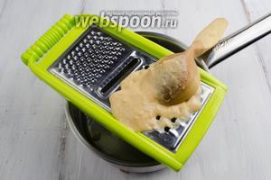 Выложить 1 ложку теста на терку. Протирать ложкой тесто. Сквозь отверстия, в кипящую воду, опадают «слёзки» теста, моментально завариваясь.