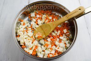 К луку добавить подготовленные морковь и корень сельдерея. Продолжить жарить ещё минут 5.
