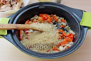 Всыпать промытый и обсушенный рис, перемешать и жарить ещё 2 минуты.