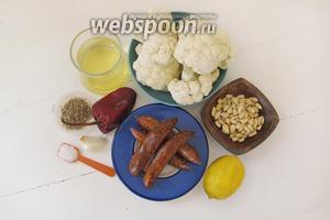 Подготовим ингредиенты для блюда: цветную капусту, колбаски, кедровые орешки, чеснок и специи. Разберём цветную капусту на соцветия.