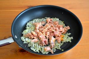 Как только лук посветлеет и станет мягче, добавьте к нему консервированного тунца (масло предварительно слить).