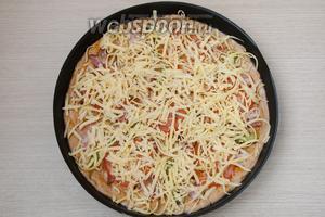 Присыпаем по желанию сушёным базиликом, а затем натираем сверху на крупной тёрке твёрдый сыр. Отправляем пиццу в разогретую до 200°С духовку на 12-15 минут.