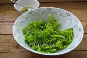 Полученной заправкой заправьте листья салата. Перемешайте руками или деревянной ложкой. Немного заправки оставьте для финального штриха.