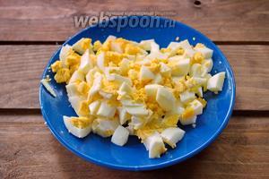 Отварные куриные яйца нарезать кубиком.