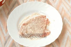 В тарелку насыпать кукурузную муку. Каждую отбивную обвалять в муке со всех сторон, лишнюю стряхнуть.
