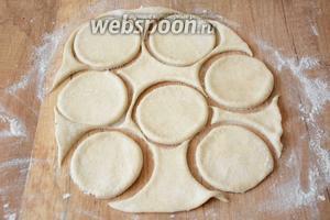 С помощью стакана выдавливаем круги. Убираем лишнее тесто.