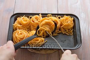 С помощью большой ложки и вилки формируем «гнёздышки» и выкладываем друг за другом в форму для выпечки.