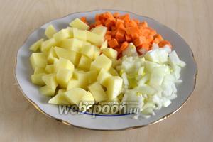 Нарежьте крупными кубиками картофель, морковь — кубиками поменьше, лук нарежьте кусочками.