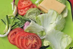 Подготовим все овощи к собиранию гамбургера: лук нарезаем длинными перьями, сыр режем на тонкие 4 куска, разбираем салат на 4 листа и нарезаем помидоры шайбами.