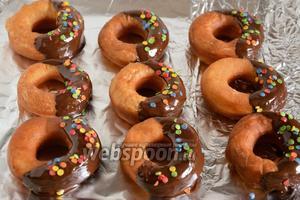 Выложите пончики на охлаждённую фольгу, украсьте кондитерской посыпкой и оставьте на 1 час в прохладном месте до застывания шоколада. Пончики готовы! Из указанных продуктов получается 24-27 пончиков.