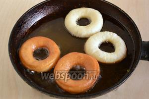 Обжаривайте пончики в большом количестве хорошо разогретого масла с двух сторон до золотистого цвета. Масла должно быть ровно столько, чтобы пончики плавали в нём, не касаясь дна сотейника.