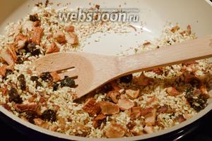 И сразу же добавим рис, всё перемешиваем и томим в сковороде, пока рис не станет прозрачный или глянцевый.