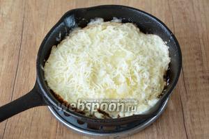 Когда омлет будет полностью готовым, посыпаем омлет оставшимся тёртым сыром, накрываем крышкой, жарим ещё около 1-2 минут, чтобы сыр полностью расплавился.