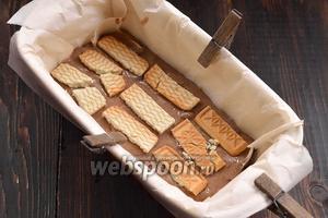 В кексовую форму, выложенную кулинарной бумагой, выложить часть теста. Сверху выложить кусочки печенья. Повторить так несколько раз.
