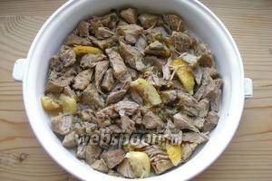 Мясо с лимоном перекладываем в форму для запекания. При этом каждый кусок мяса разделяем по волокнам на несколько частей. Сбрызгиваем соусом со дна кастрюли — буквально 2-3 ст. л.