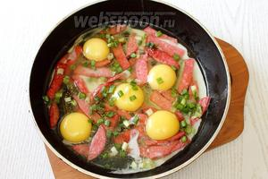 Солим по вкусу, посыпаем измельчённой зеленью. Накрываем сковороду крышкой и жарим яичницу до готовности в течение 3-5 минут, на среднем огне.