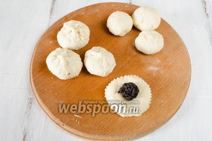 Разложить маковую начинку, 5-7 г на каждую лепёшку из теста. Свернуть тесто с начинкой в мешочек. Скатать булочку шариком.