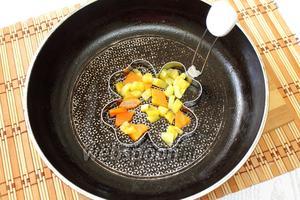 Перекладываем цукини с морковью на тарелку. На сковороду ставим форму для яичницы, заполняем её 1/5 цукини и морковью.