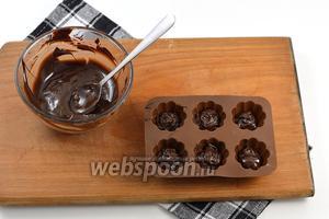 В маленькие формочки для конфет (можно использовать формочки для льда) выложить по 1 столовой ложке шоколада.