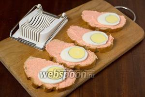 Яйцо разрезаем на ровные кружочки с помощью яйцерезки и укладываем на хлеб с икрой с одной стороны.