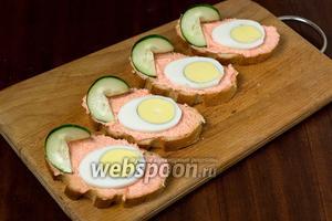 Ставим огурец на бутерброды, разъединив в разные стороны разрезанные части.