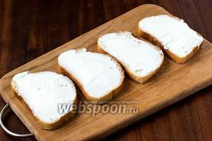 Ломтики белого хлеба намазываем сливочным сыром.
