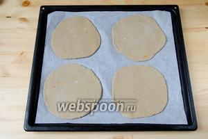 Выложить лепёшки на противень, застеленный пергаментом и поставить их сушиться в духовку (180°С) примерно на 25-30 минут.