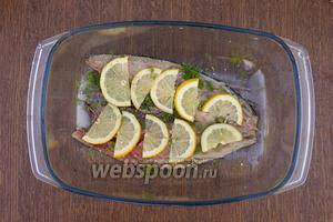 Филе 1 рыбы положить в ёмкость для маринования, кожицей вниз, посолить, приправить приправой, выложить дольки лимона и измельчённый укроп.