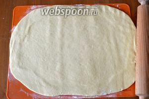 Подошедшее тесто выложить на рабочую поверхность и раскатать в прямоугольник толщиной около 7 мм.
