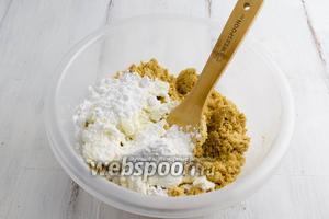 Добавить к масляной крошке творог и сахарную пудру. Перемешать. Замесить тесто руками.