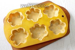 Тесто тонко раскатываем, толщиной 2-3 мм, вырезаем кружочки чуть больше диаметра размера формочек. Выкладываем тесто, прижимаем.