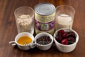 Для приготовления ленивой овсянки нам нужны следующие ингредиенты: овсяные хлопья для варки, кокосовое молоко, питьевой натуральный йогурт, свежая черешня, мёд и шоколадные капли.