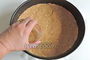 На дно разъёмной формы выкладываем печенье и утрамбовываем. Удобно это делать со стаканом, плотно придавливая его ко дну.