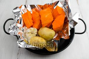 Тыкву, картофель и чеснок запечь в духовке. Хорошо это сделать заранее. Запекать в фольге при температуре 200°C до готовности.