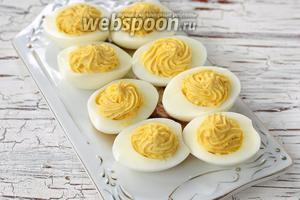 Наполнить яичные белки полученной смесью. Можно выдавить её фигурно с помощью кулинарного шприца.