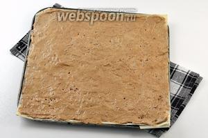Разделить тесто на 3 части. Форму размером 20х20 см выложить кулинарной бумагой. Смазать бумагу сливочным маслом. Выложить 1/3 часть теста и разровнять по всей площади с помощью ножа.