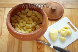 Берём горшок и смазываем его внутри растительным маслом. Нарезаем кубиками картофель и отправляем в горшок.