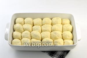 Сложить плотно пирожки в смазанную подсолнечным маслом форму для выпечки. Накрыть полотенцем и оставить в тёплом месте на 25-30 минут.