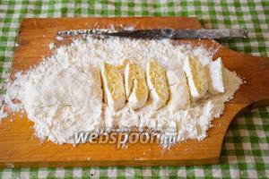 Припылим доску мукой и выложим тесто. Скатаем колбаску и нарежем её на сегменты около 1 см толщиной!
