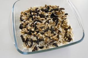 Сверху выложите чернослив, нарезанный соломкой, и рубленные орехи.