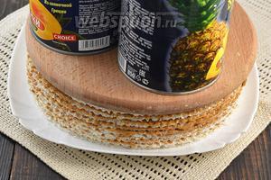 Верхнюю сторону последней вафли кремом не смазывать. На вафельный торт сверху выложить кухонную доску, а на неё — небольшой груз. Оставить в таком состоянии на 2 часа.