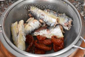 Сардины и вяленые томаты выложить в ситечко и дать стечь маслу.