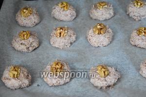 Выложить ложкой для мороженого печенье на противень с пергаментом. Печенье украсить половинками орехов и выпекать в разогретой до 180°С духовке 15 минут.