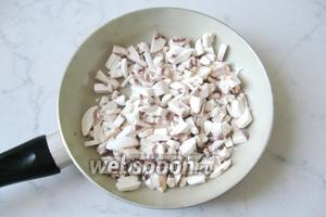 Выложить нарезанные грибы на сковороду с подсолнечным маслом. Тушить 7-10 минут, пока не испарится жидкость.