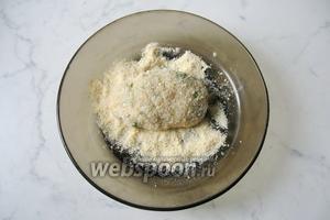 Заворачиваем масло в фарш, придаём продолговатую форму и кладём в панировочные сухари.