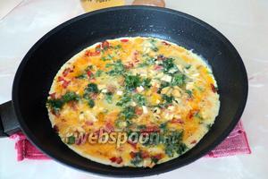 Влейте яичную смесь, присыпьте Сулугуни зеленью, накройте сковороду крышкой, отправьте на умеренный огонь на 4 минуты. Подавайте ароматный омлет с чашечкой кофе и тостами.